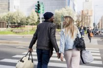 Happy smiling multi ethnic couple crossing road in street and carrying bags — Stock Photo