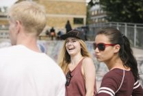 Three male and female friends laughing in city skatepark — Foto stock