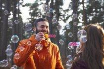 Giovane coppia soffiando bolle nel bosco — Foto stock