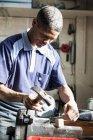 Молодой человек забивает гвоздь в мастерской — стоковое фото