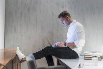 Junger Geschäftsmann auf Schreibtisch Tippen auf laptop — Stockfoto
