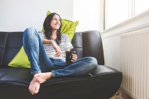 Femme assise sur le canapé tenant la tasse de café, regarde par la fenêtre souriant — Photo de stock