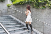 Woman ascending steps using digital tablet — Stock Photo