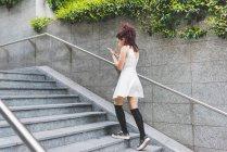 Woman ascending steps using digital tablet — Stock Photo
