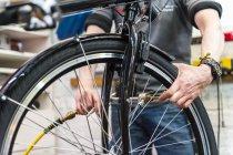 Mechanic repairing bicycle in workshop — Stock Photo