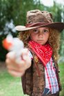 Girl in cowboy hat with toy pistol — Stock Photo