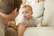 Linda niña de ojos azules en el sofá mirando a su padre — Stock Photo