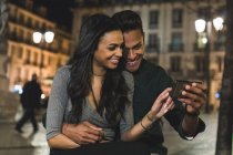 Couple in city, at night, looking at smartphone, Lisbon, Portugal — Stock Photo