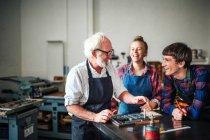 Artesano senior riéndose con joven artesano y artesana en taller de tipografía - foto de stock