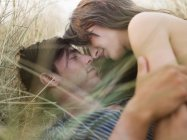 Couple lying in grass kissing — Stock Photo
