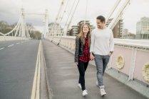 Coppia giovane felice passeggiando sul ponte, Battersea Park, Londra, Regno Unito — Foto stock