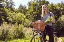 Portrait of young woman on bicycle gazing from rural dirt track — Stock Photo