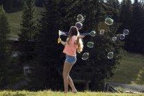 Jovem mulher soprando bolhas em campo, Sattelbergalm, Tirol, Áustria — Fotografia de Stock