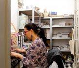 Женщины малого бизнеса владельца, набрав на клавиатуре компьютера в Сувенирный магазин склад — стоковое фото