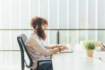 Junge männliche Hipster mit roten Haaren und Bart Tippen auf Laptop am Schreibtisch — Stockfoto