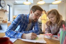 Mid adult man and daughter colouring at table in kitchen — Stock Photo