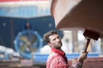 Male ship painter roller painting ship hull in ship painters yard — Stock Photo