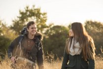 Junge Paare, die durch Feld — Stockfoto