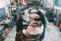 Мужская команда по металлообработке молотит медь на кузнице — стоковое фото