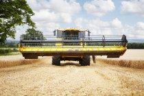 Harvester working in crop field — Stock Photo