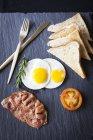 Vista superiore di pane tostato con pancetta, uova fritte e pomodori colazione sull'ardesia — Foto stock