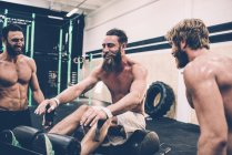 Three male cross trainers chatting in gym — Stock Photo