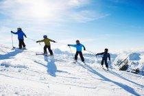 Children climbing snowy mountainside — Stock Photo