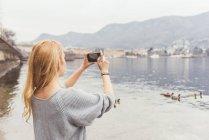Молодая женщина, фотографирование от озера, озеро Комо, Италия — стоковое фото