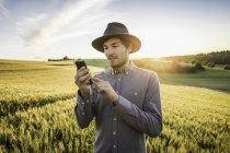 Человек, стоящий в поле и использующий смартфон — стоковое фото
