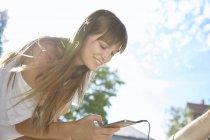 Jovem mulher ao ar livre, usando smartphone, sorrindo — Fotografia de Stock