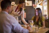 Serveuse au service des clients dans un restaurant moderne — Photo de stock