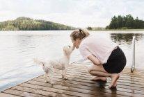 Woman kissing coton de tulear dog on pier, Orivesi, Finland — Stock Photo