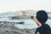 Rear view of woman using smartphone to photograph beach, Stintino, Sassari, Italy — Stock Photo
