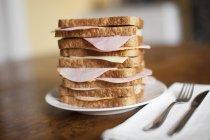 Pila di panini al prosciutto sul piatto con posate — Foto stock