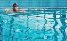 Мужчина плавает в закрытом бассейне — стоковое фото