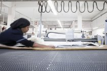 Работница фабрики готовит текстиль для машин на швейной фабрике — стоковое фото