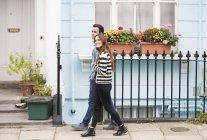 Vue latérale du couple marchant dans la rue souriant — Photo de stock