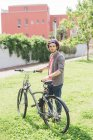 Счастливый кавказский человек с велосипедом в парке — стоковое фото