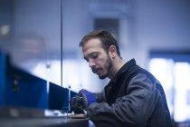 Молодой мужчина Инженер, осматривающий тяжелую технику — стоковое фото