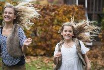 Две сестры с длинными светлыми волосами бегают в осеннем саду — стоковое фото