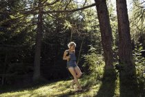 Середині дорослих жінка, що сидить на ліс гойдалки, Sattelbergalm, Тіроль, Австрія — стокове фото