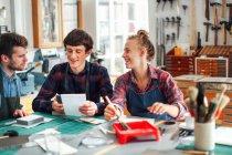 Молода Майстриня тримає кисть і сміятися і посміхатися з двома молодими майстрами в творчих друк студії — стокове фото