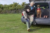 Homem e cão sentado no carro de inicialização remover botas wellington — Fotografia de Stock