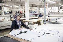 Работник фабрики удаляет нарезанный текстильный рисунок из машины для резки узоров на швейной фабрике — стоковое фото