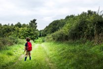 Rear view of boy with backpack on rural landscape — Stock Photo