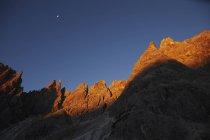 Formations rocheuses couvertes dans la lumière du coucher du soleil avec la lune dans le ciel — Photo de stock