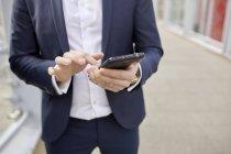 Mittelteil von Geschäftsmann auf Fußgängerbrücke SMS auf Smartphone, London, Großbritannien — Stockfoto