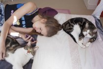 Teenage girl lying with cats and using smartphone — Stock Photo
