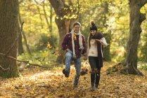 Jovem casal caminhando pela floresta de outono — Fotografia de Stock