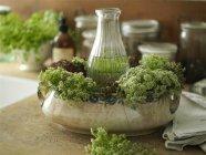 Размещение цветов с полевыми цветами и винтажной миской на кухонном столе — стоковое фото